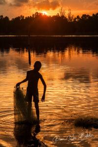 Ankaninofy, Madaagscar, November 17, 2016:  A Malagasy fishrman taking back his fishing net at sunset in the Pangalanes Canal, east of Madagascar