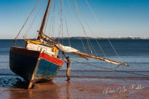 Un marin malgache et sa goélette à marée basse à Analalava, Madagascar