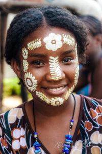 Portrait d'une jeune femme malgache et son masque traditionnel Sakalava à Nosy Be, Madagascar