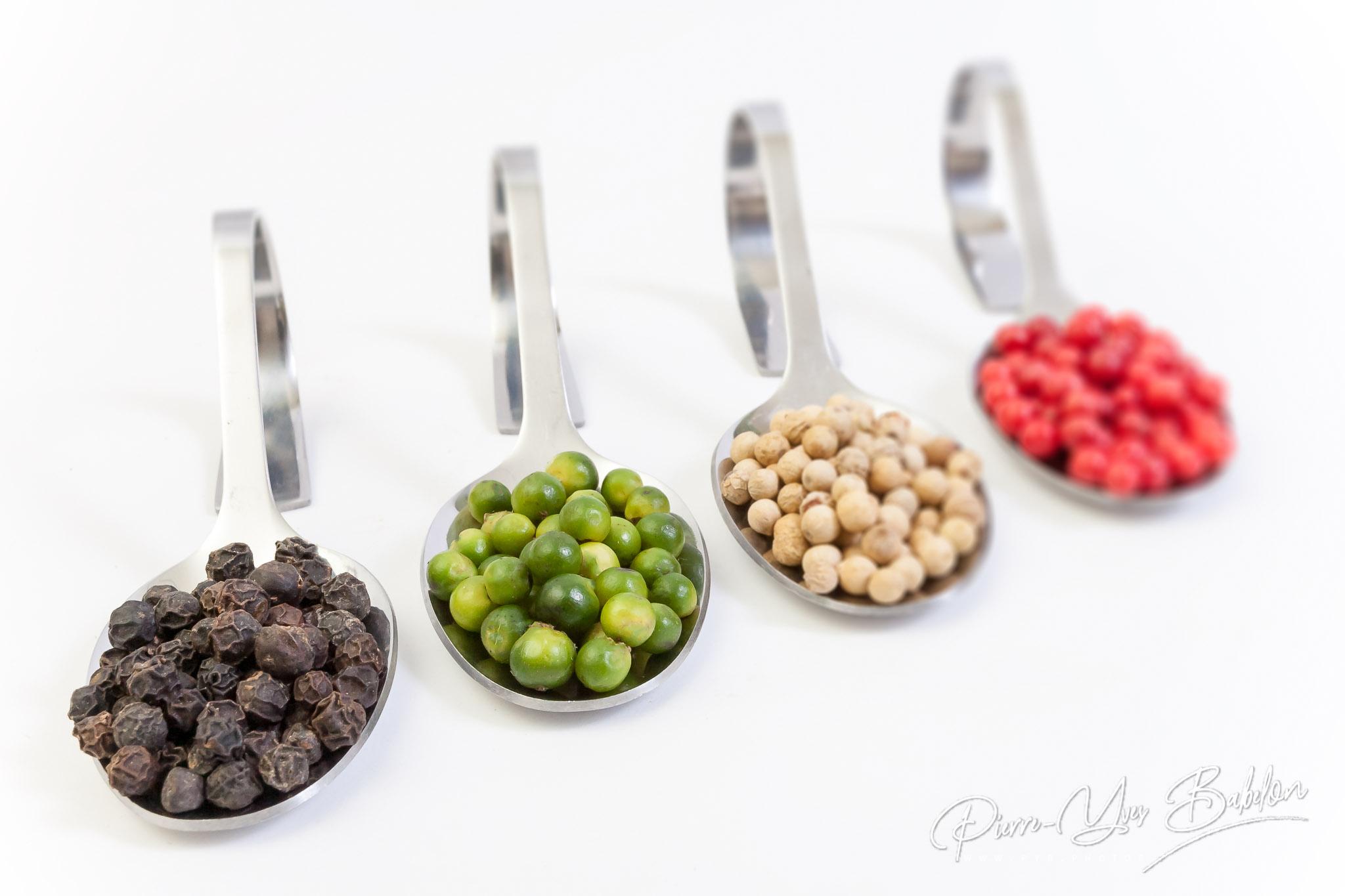 Quatre sortes de grains de poivre dans des cuillères métalliques