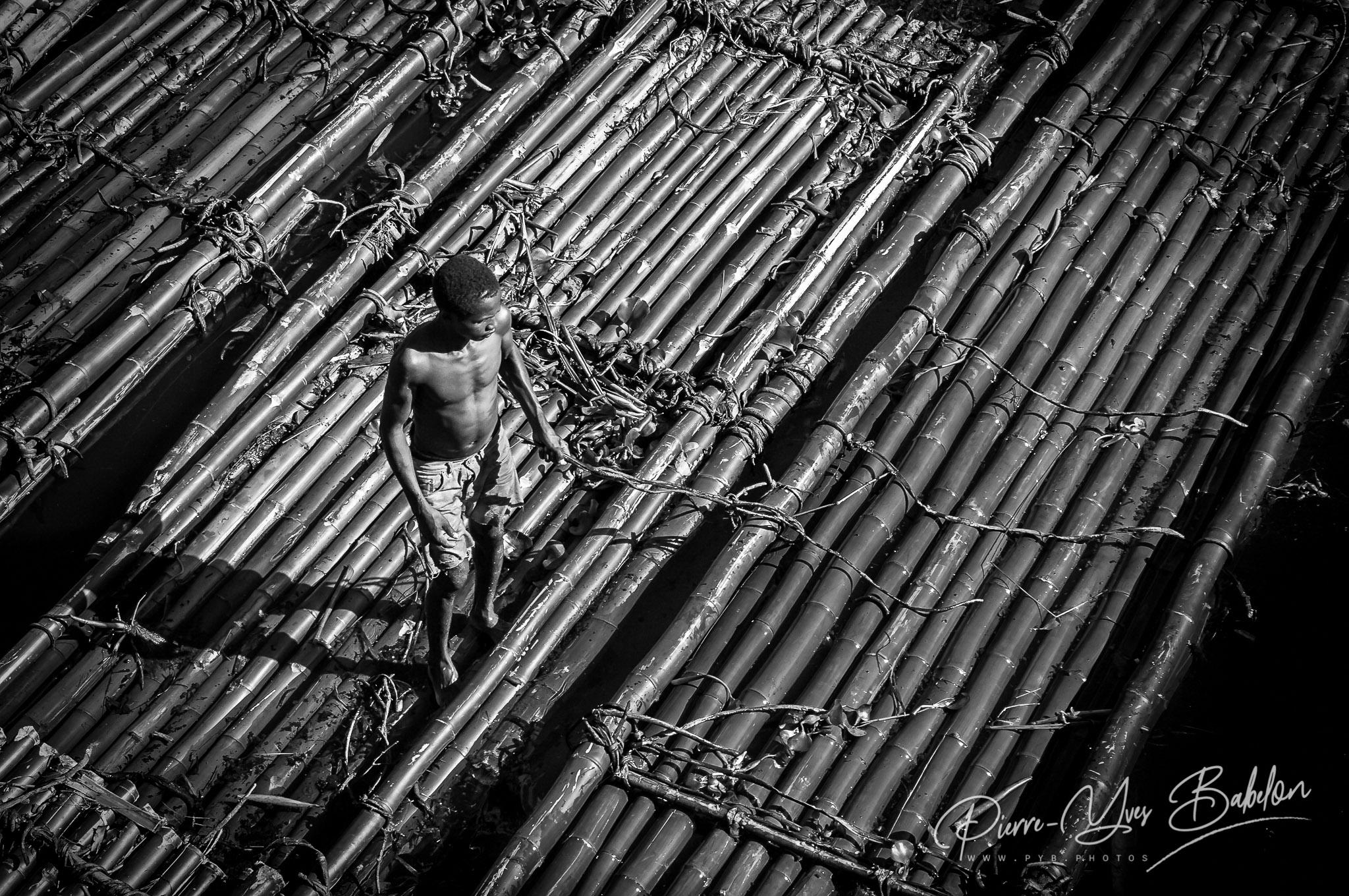 Un homme sur son radeau de bambou, Canal des Pangalanes, Madagascar