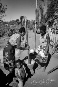 Famille malgache pilant de manioc au mortier