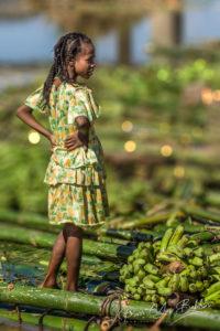 A Malagasy young girl collecting bananas with bamboo rafts on the Pangalanes canal, Eastern Madagascar. Une jeune fille malgache collecteuse de bananes en radeau de bambous sur le canal des Pangalanes dans l'Est de Madagascar. Photo by @pierivb.