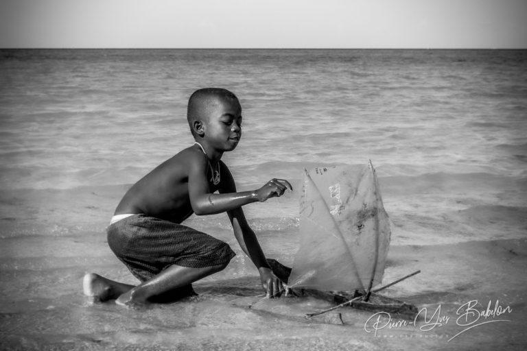 Enfant malgache Vezo jouant avec sa pirogue