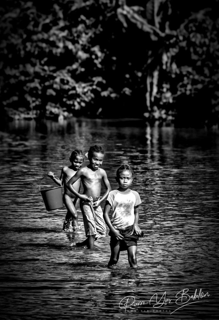 Trois petites filles malgaches marchant dans la rivière