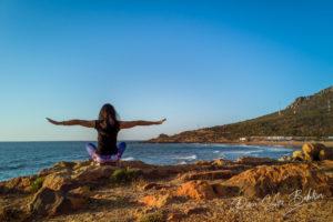 Une femme pratiquant la posture du lotus du Hatha yoga au coucher du soleil devant la plage.